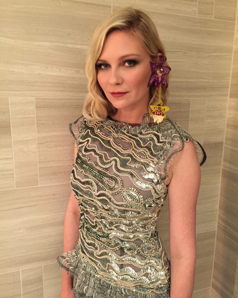 Kirsten Dunst wears earrings with real orchids by Rodarthe